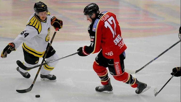 Luleå Hockeys Bill Sweatt mot Brynäs Jonathan Pudas. Foto: Alf Lindbergh/Pressbilder.