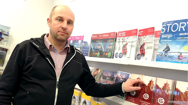 Lars Mandahl visar olika turistbroschyrer.