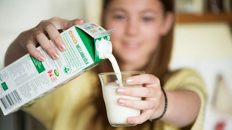 Kvinna häller upp ett glas mjölk.