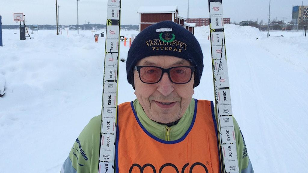 Lars-Erik Persson i sin veteranväst och klisterlappar från åtta Vasalopp på skidorna. Foto: Tova Nilsson/Sveriges Radio