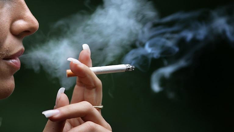 kvinna som blåser ut cigarettrök.