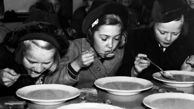 Svartvit bild på tre flickor som äter med sked från tallrikar i en skolmatsal.