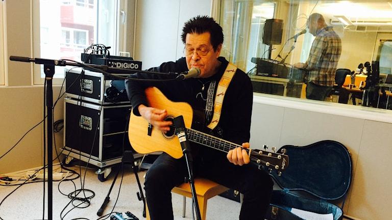 """Georg """"Jojje"""" Wadenius spelar akustisk gitarr i P4 Norrbottens studio."""