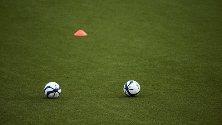 Två fotbollar och en kona på en konstgräsplan.