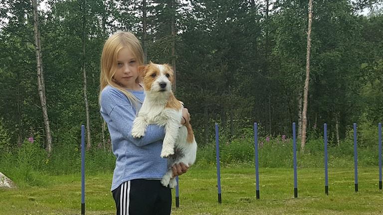 Tilde Holmqvist med hunden Polly i famnen framför agilitybana.
