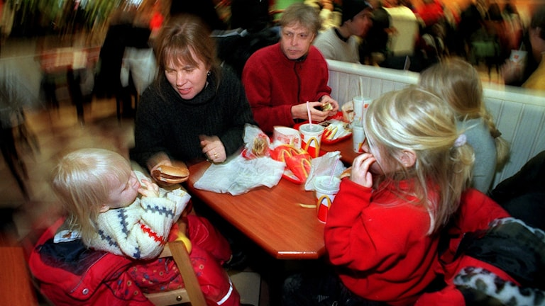 Barnfamilj äter på hamburgerrestaurang.