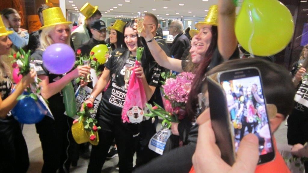 Boden Handboll firar i guldhattar och med champagne vid hemkomsten efter elitserieavanceanget.