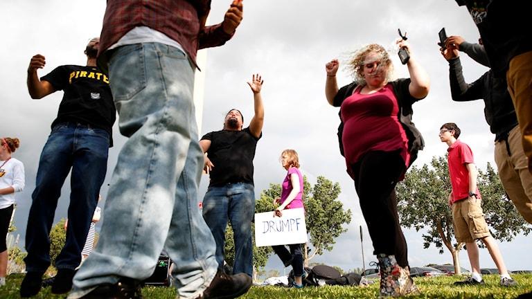 En grupp sommarklädda människor dansar utomhus.
