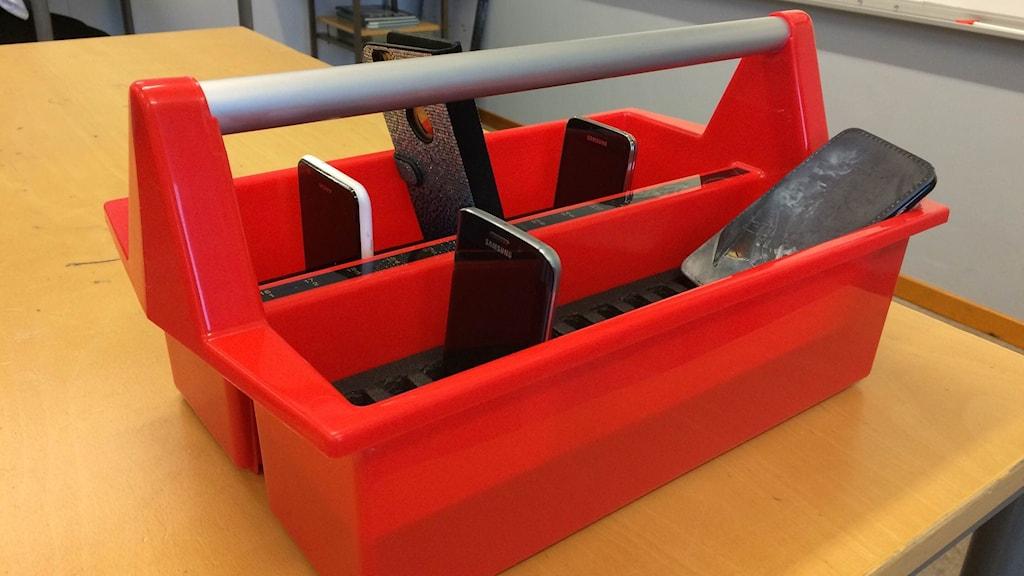 Telefoner i en röd låda.