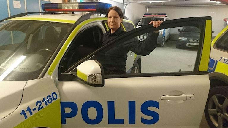 Polisen Maria Lestander vid en polisbil i ett garage.