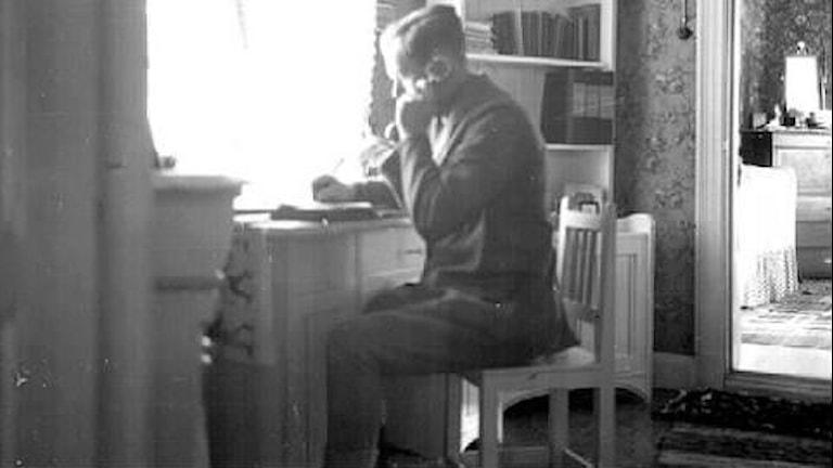 En man pratar i gammal telefon.