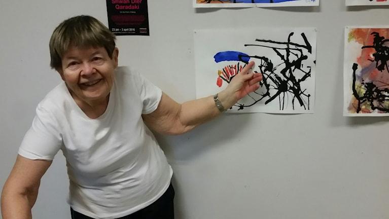 Lena Isaksson visar upp ett konstverk på FUB-uställningen.