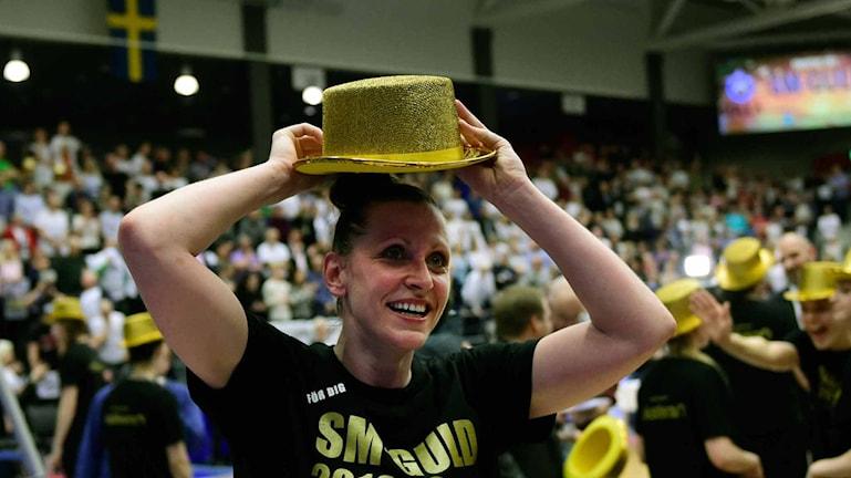 En glad Anna Barthold sätter på sig sin guldhatt
