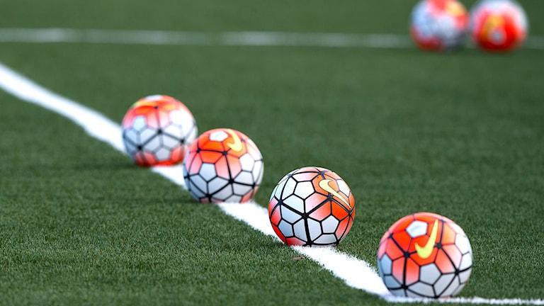 Fotbollar ligger på linje på en fotbollsplan.