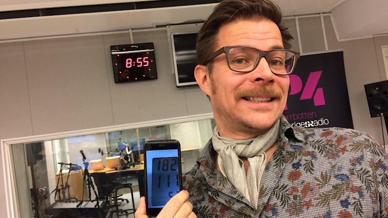 Olov Stenlund visar upp en bild av blodtrycksmätaren som visar siffrorna 182 och 111. Foto: Tova Nilsson/Sveriges Radio