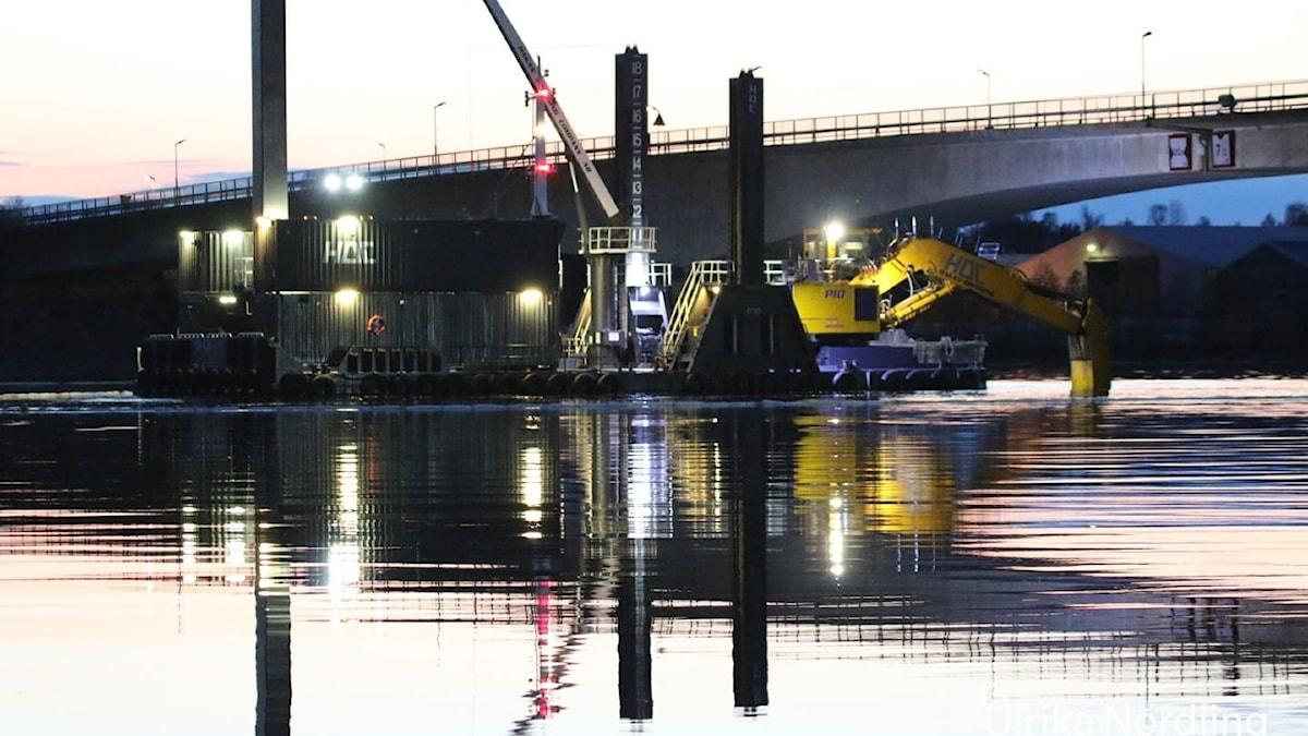 Ett muddringsarbete pågår i vattnet vid en bro. Stora maskiner och lampor speglas i vattenytan.