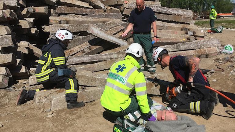 Räddningspersonal försöker rädda mannen som är skadad, men allt är bara övning.