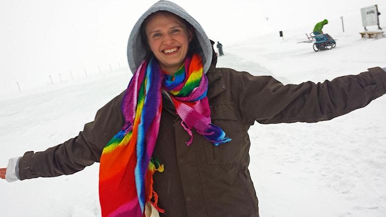 Kvinna i regnbågsscarf ute på isbanan