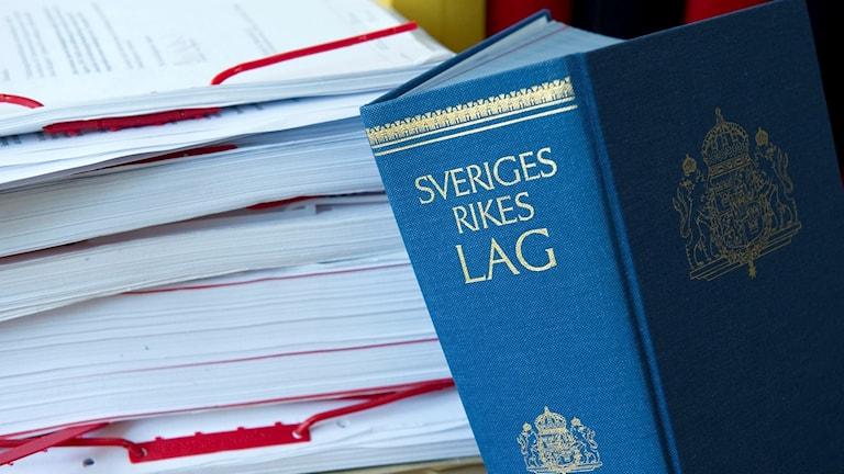 Lagboken och en lunta med papper.