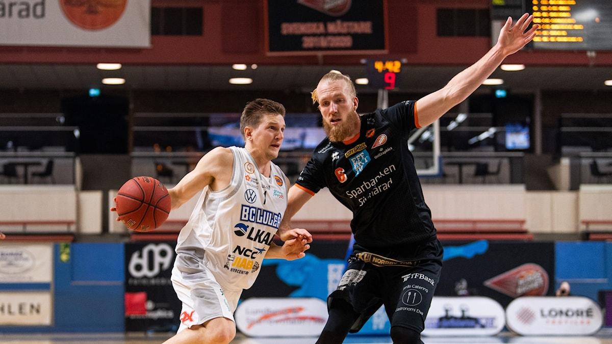 Luleås Adam Rönnqvist och Borås William Gutenius under basketmatchen i herrarnas SBL mellan Borås och Luleå den 4 december 2020 i Borås.