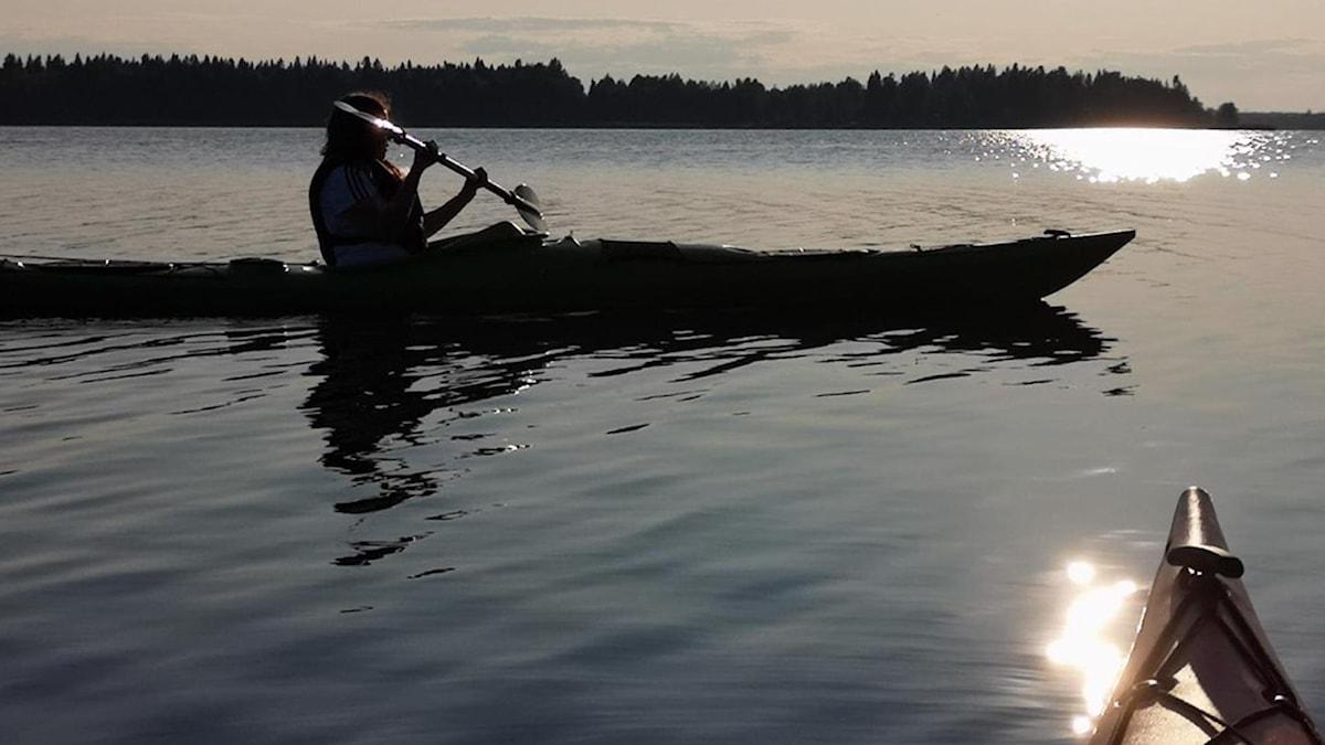 En kanot i motljus i skärgården. Fören från fotografens kanot sticker fram i underkant.