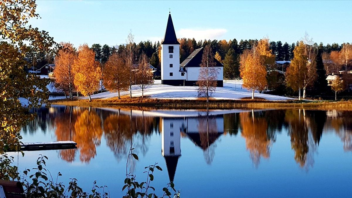 Kyrkan i Vuollerim speglas i vattenytan. Ramas in av träd i höstfärger.
