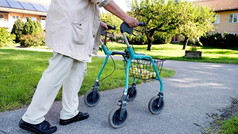 Äldre person går med rullator.
