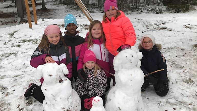 Barnen på Knut Lundmarkskolan visar uppsina snögubbar.