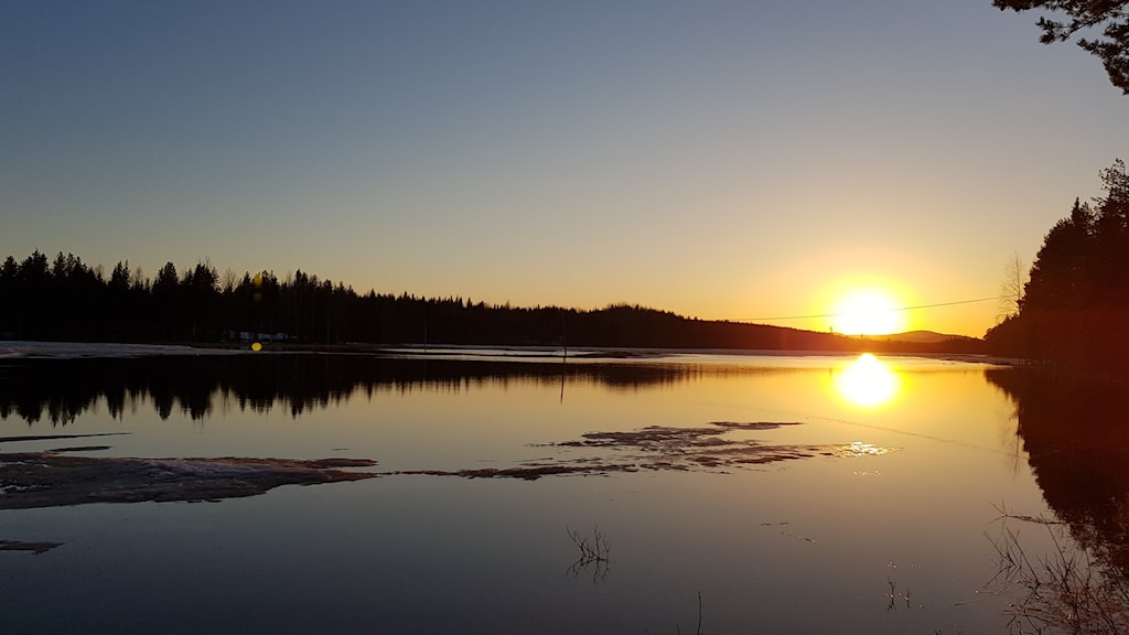 Solnedgång reflekteras i den mörka vattenytan. Berg och skog i bakgrunden.