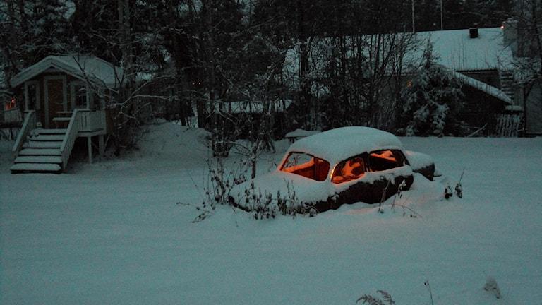 En översnöad gammal Fiat med belysning i en trädgård.