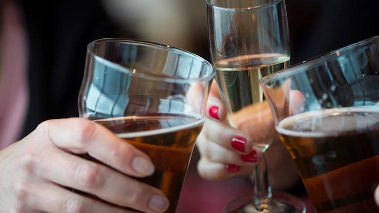 Tre glas som skålar med öl och champagne.