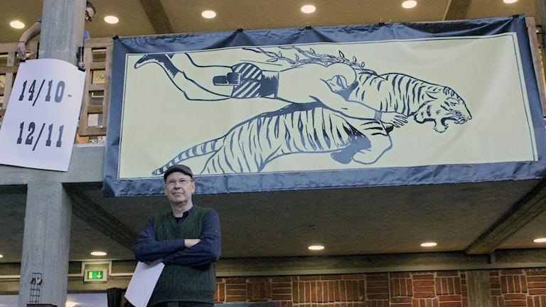 Martin Goldbeck-Löwe framför en av Wilson McCoys teckningar av Fantomen, som ställs ut i Kiruna stadhus.