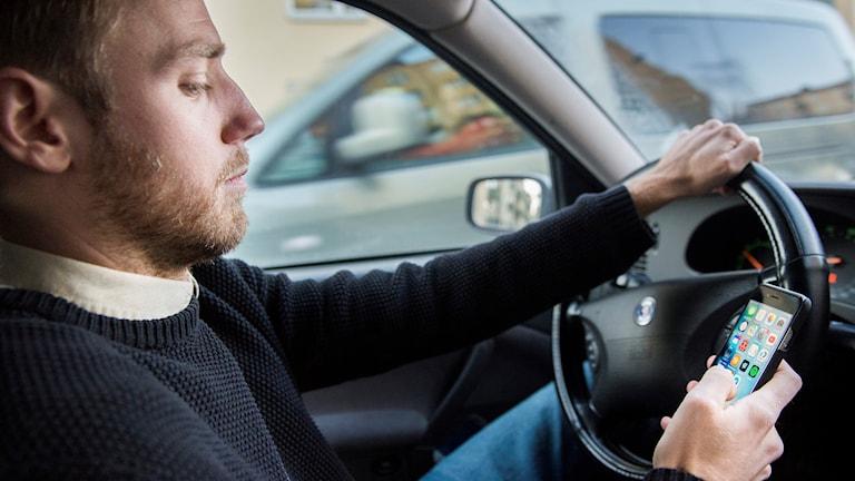 En man kör bil och använder sin mobil  .