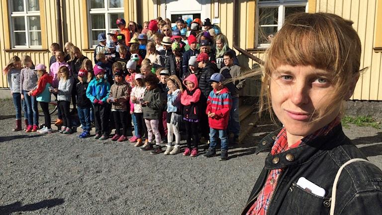 Liv Shange Moyo, förälder till barn på Svartöstadsskolan, står utanför skolan med en grupp elever i bakgrunden.