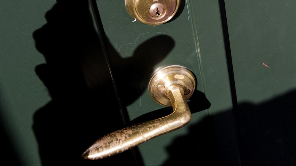 Silhuetten av en hand mot ett dörrhandtag på en grön dörr.