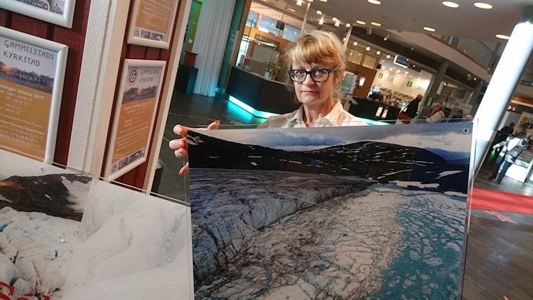 Maria Söderberg håller upp en av sina bilder på glaciären Salajekna.