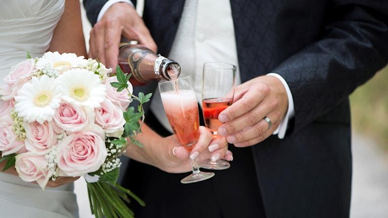 Brudpar med brudbukett häller upp och skålar i rosa champagne.