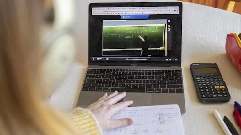 En kvinna sitter vid dator och får undervisning på distans.