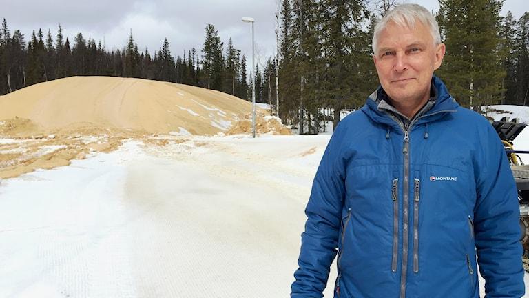 Stefan Nieminen framför en hög med snö som har täckts med sågspån. Foto: AlexanderLinder/Sveriges Radio.