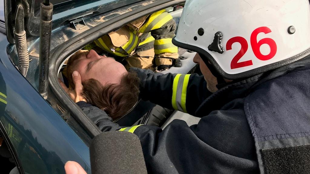 Livräddning genom en trång passage ur baklucka. Arjeplogs Hans-Olov Wikström lyfter fram kurskamraten Robin från Överkalix.
