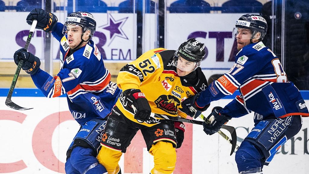 Växjös Hardy Häman Aktell och Robert Rosén samt Luleås Karl Fabricius under ishockeymatchen i SHL