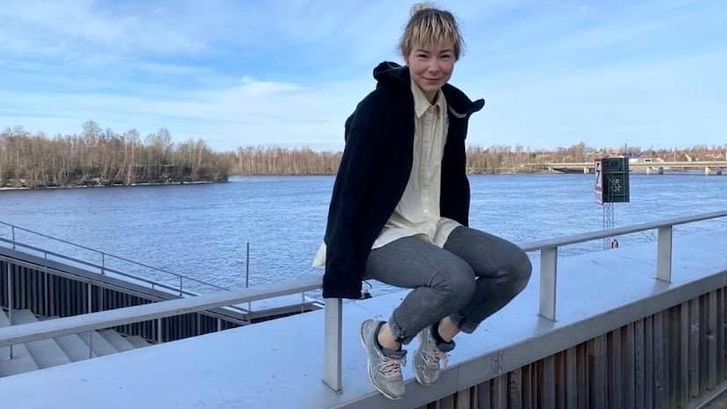 En person sitter på ett räcke. Bakom syns Umeåälven.