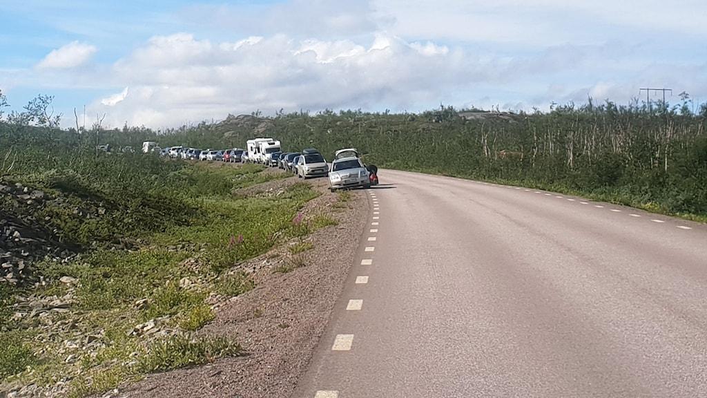 Bilar står parkerade längs E10, nära stigen till Rissajávri/Trollsjön.