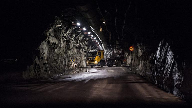 Bild på lastbil inne i mörk gruva.