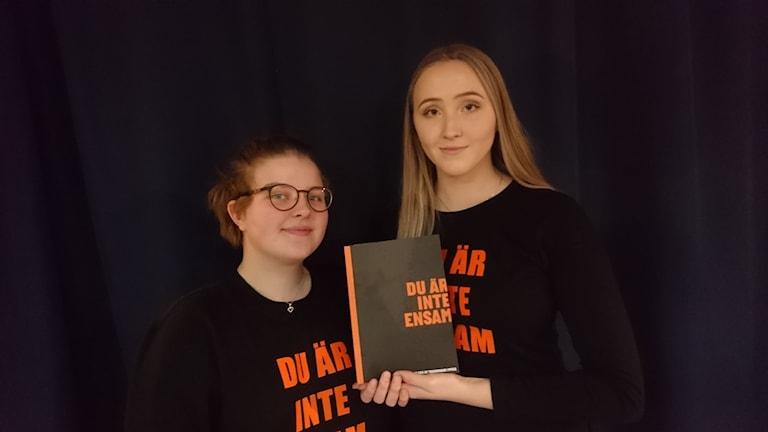 """Thea Määttä står bredvid Linnea Eriksson som håller upp boken """"Du är inte ensam""""."""