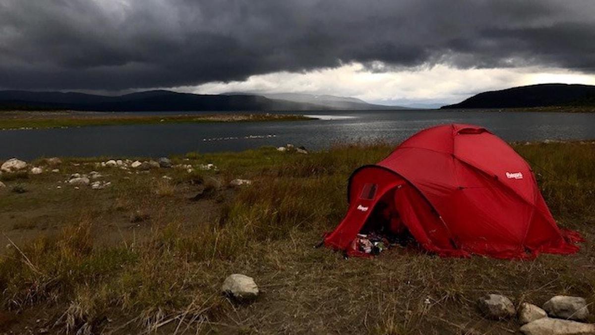 Ett rött tält på fjället under mörkgrå moln.