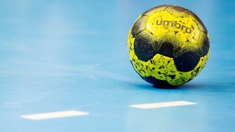 En handboll liggande på hallgolvet.