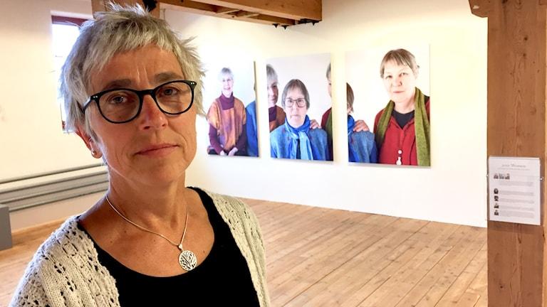 Ingela Ögren Weinmar framför tre av fotona från utställningen.