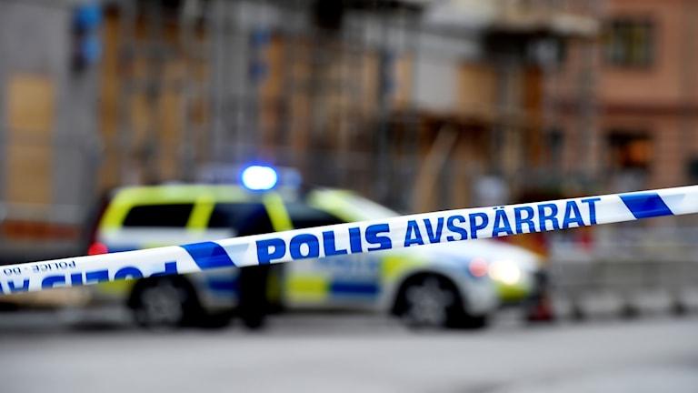 Polisavspärrning med patrullbil i bakgrunden.