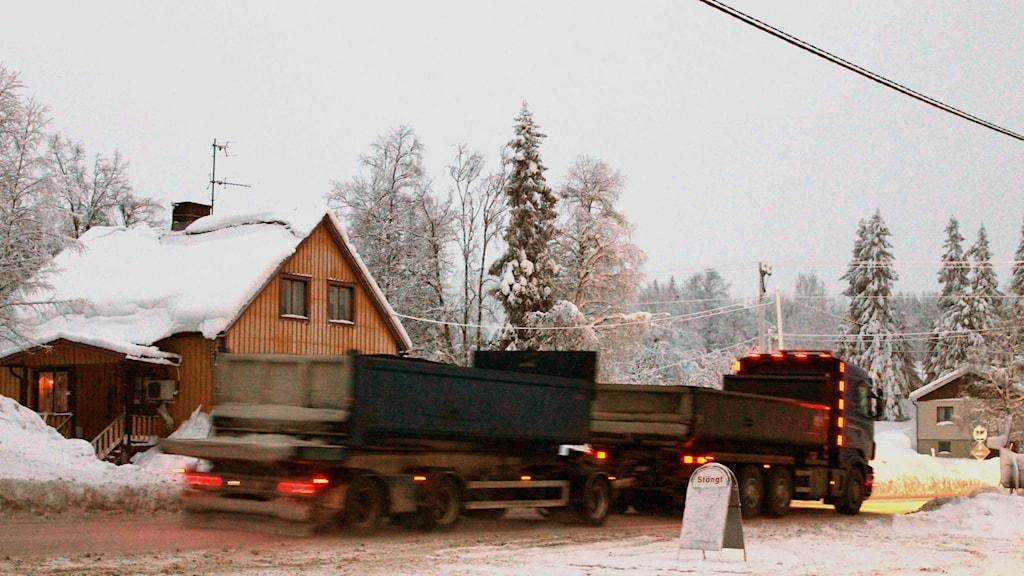 Tunga lastbilar rullar genom Masugnsbyn. Foto: Alexander Linder/ Sveriges Radio.
